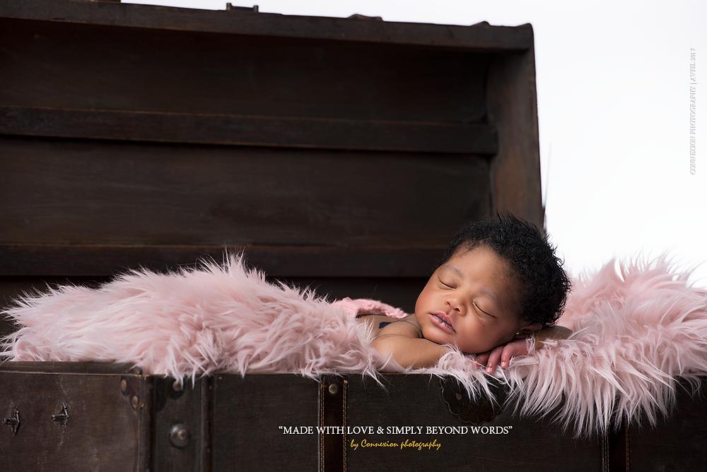 bébé noir dormant dans une malle couvert d'une fourrure