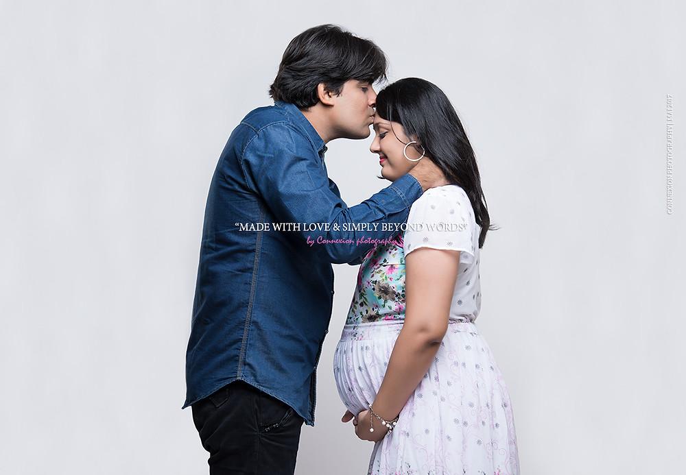 mari embrasse le front de sa femme enceinte tous les deux debout