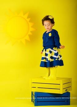 Fille noire debout sur caisse jaune