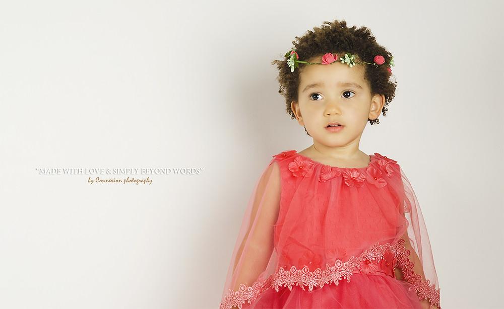 belle petite fille métisse en robe rouge assise dos au mur