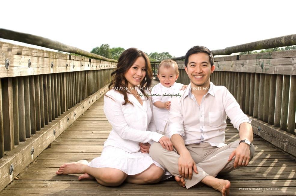 Petite famille chinoise sur ponton dans un parc, enfant debou