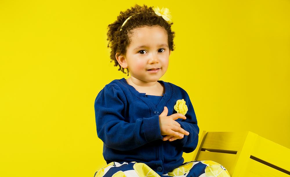 petite fille métisse assise sur une caisse en bois devant fond jaune