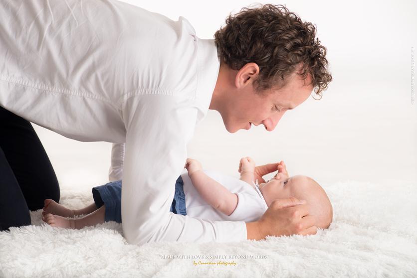 Papa à genoux au dessus de son bébé blanc