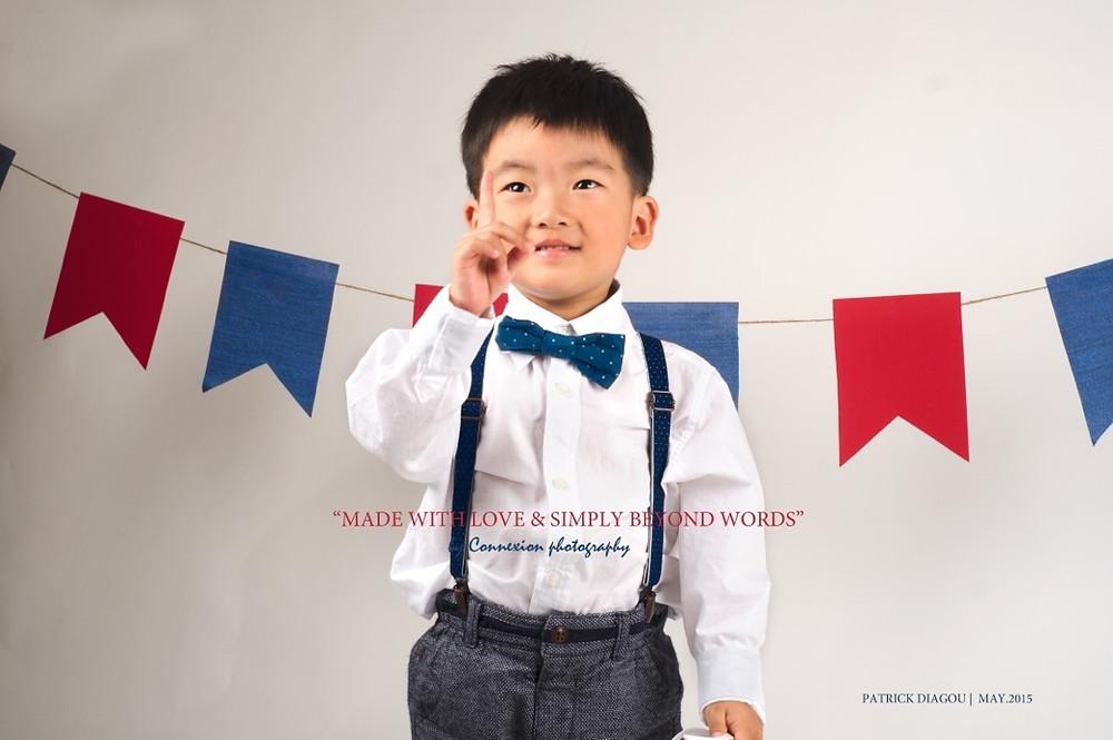 Enfant asiatique debout en tenue de soirée la main droite levée