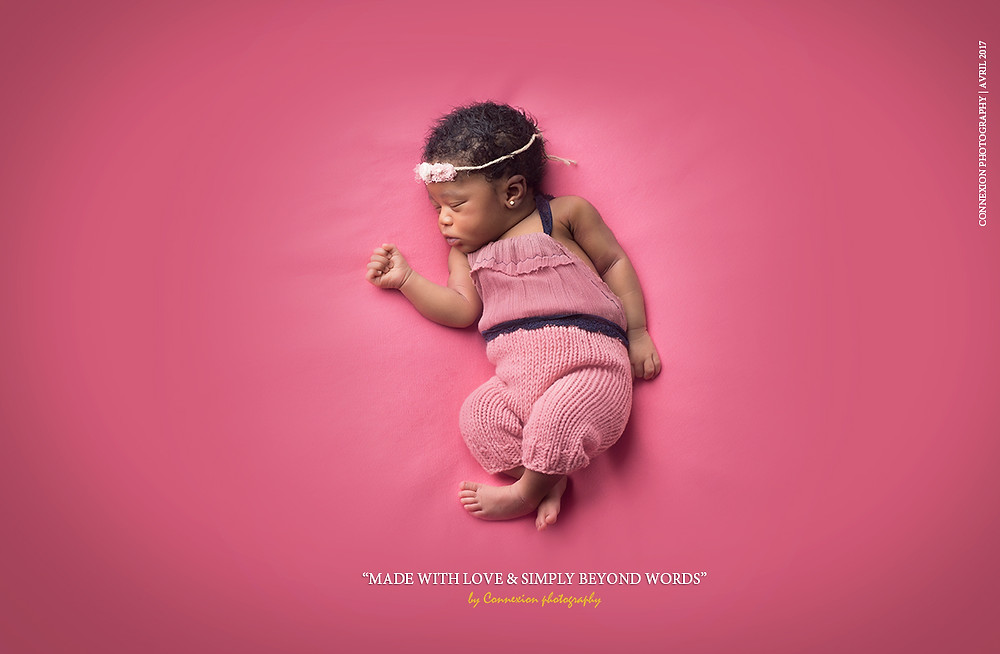 bébé noir habillé en rose endormi sur le dos sur fond rose