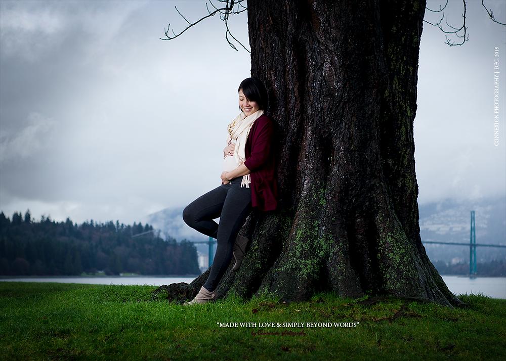 femme enceinte blanche dans parc adossée contre un arbre