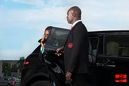 Homme noir ouvre la porte de la voiture de son employeur