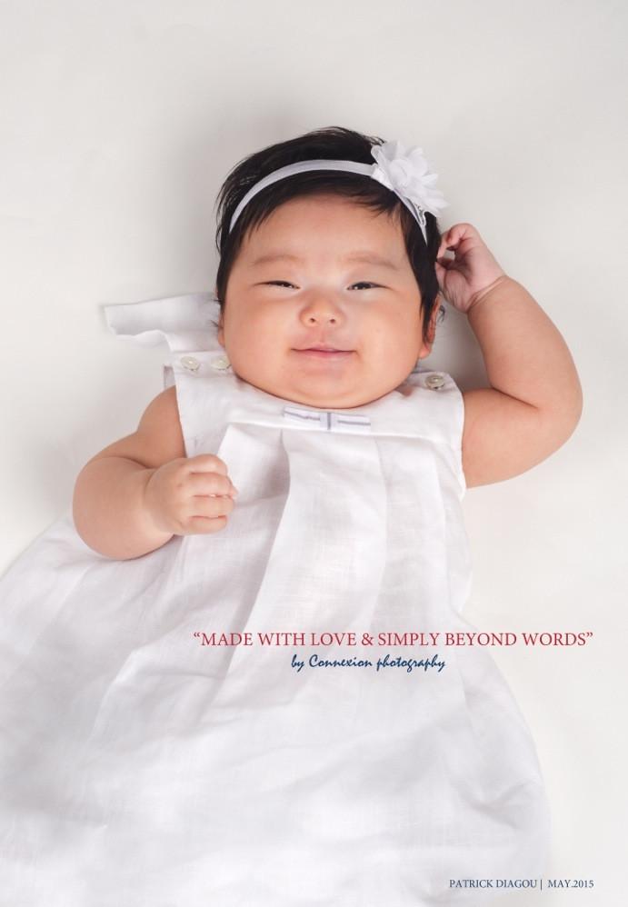 Petite fille asiatique souriante en robe blanche couchée sur le dos sur fond blanc