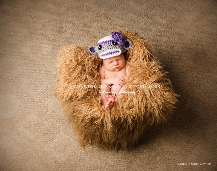 Bébé blanc nu avec bonnet en laine violet endormi sur fourrure beige