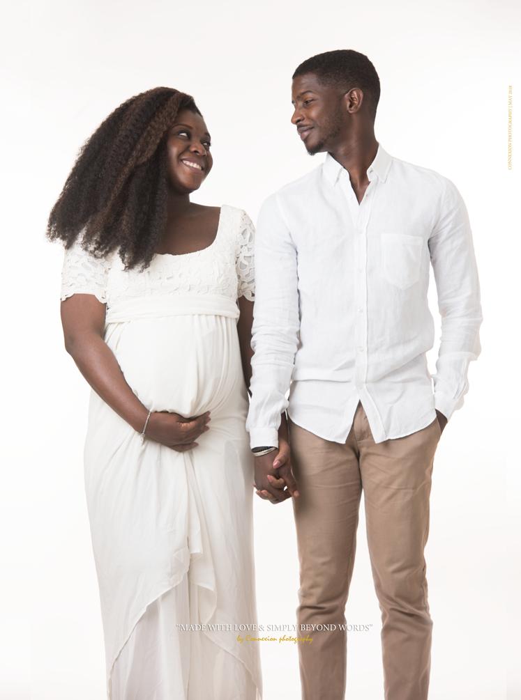 couple noir avec femme enceinte debout se regardant main dans la main avec le sourire