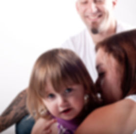 Family photo mom kissing toddler girl looking straight