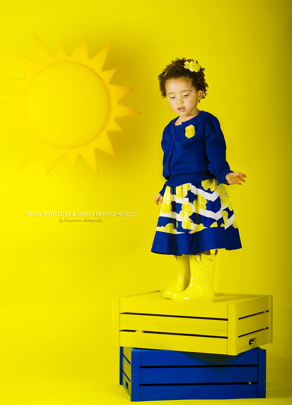 petite fille métisse debout sur une caisse en bois sur fond jaune