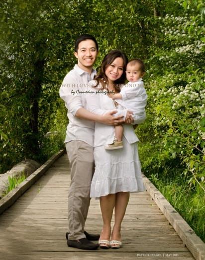 Petite famille chinoise debout dans un parc avec bébé dans les mains de maman