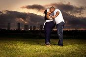Un couple de noirs avec femme enceinte s'embrassent sur une pelouse au couché du soleil