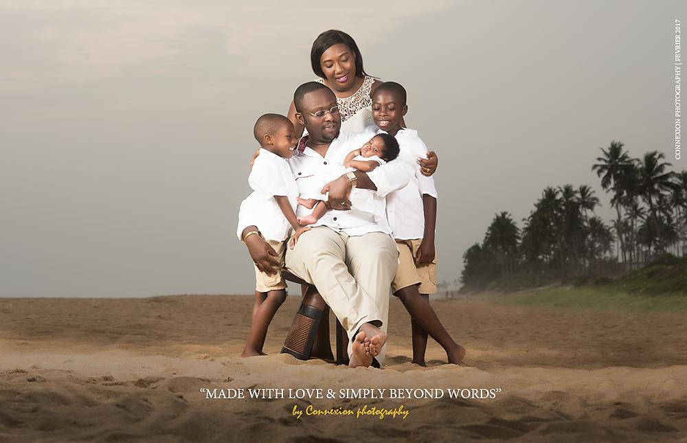 photo de famille noire regardant bébé dans les bras de papa assis