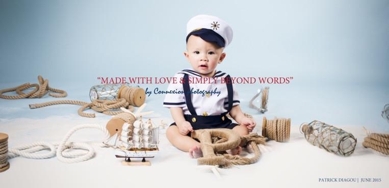 Bébé blanc en tenue de marin avec képi,souriant assis sur le sol dans une décor marin sur fond bleu