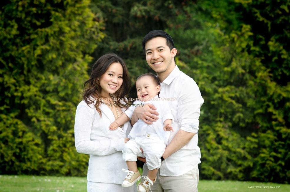 Petite famille chinoise debout dans un parc avec bébé entre maman et papa