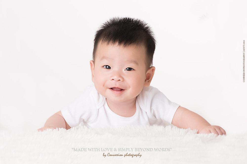 bébé asiatique couché sur le ventre sur fourrure blanche