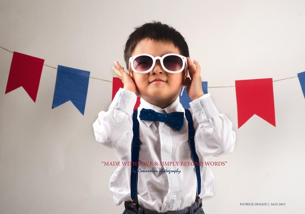 Enfant asiatique debout en tenue de soirée avec des lunettes de soleil
