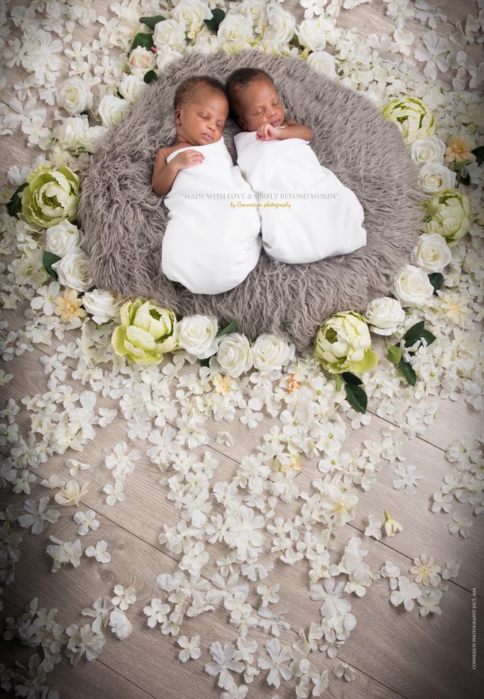 Bébés jumeaux noirs endormis sur une fourrure grise entouré de fleurs