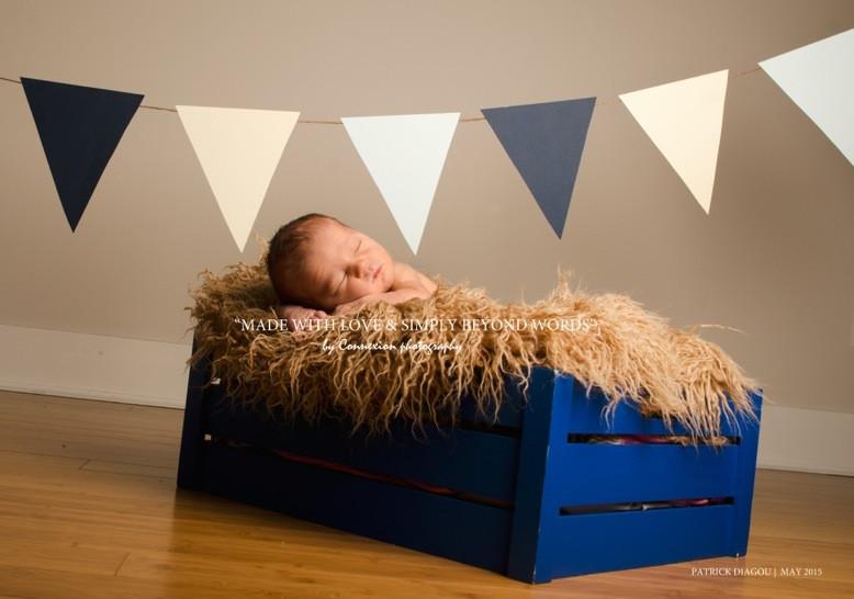 Bébé blanc dort sur fourrure beige dans une caisse bleue