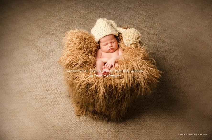 Bébé blanc nu avec bonnet en laine beige endormi sur fourrure beige
