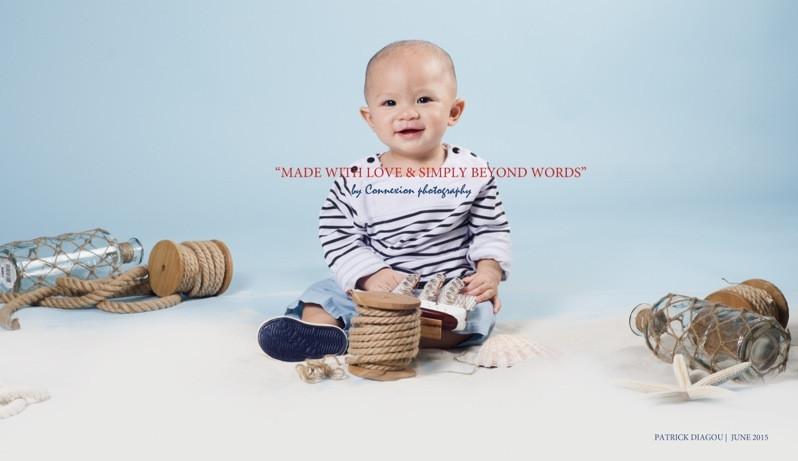 Bébé blanc en tenue de marin à rayures noires et blanches,souriant, assis sur le sol dans décor marin sur un fond bleu