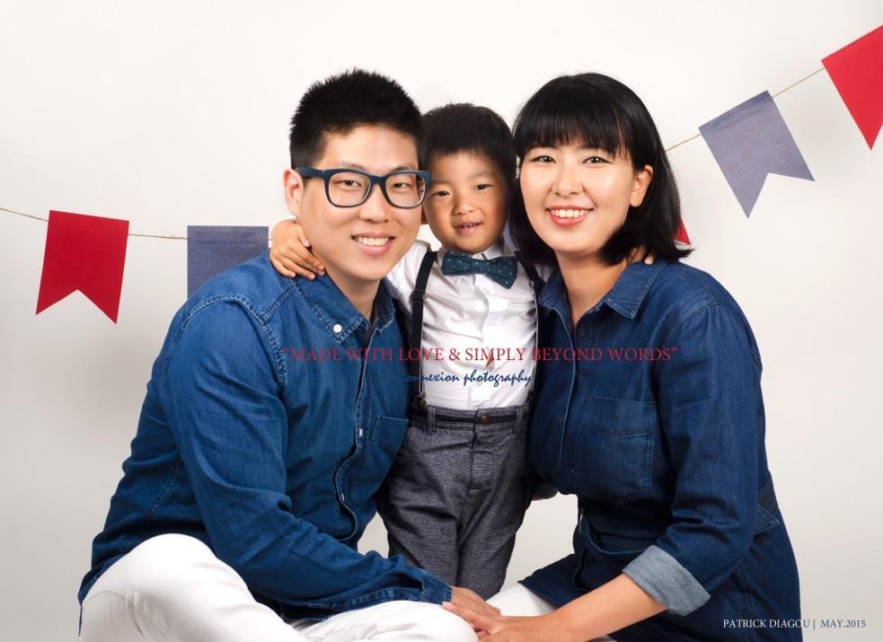 Petite famille d'asiatiques, papa et maman assis sur le sol leur enfant debout entre eux
