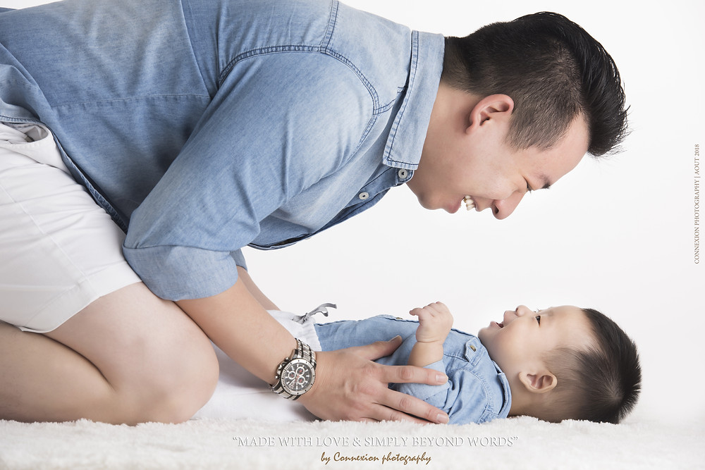 Papa et enfant asiatique couchés sur fourrure blanche