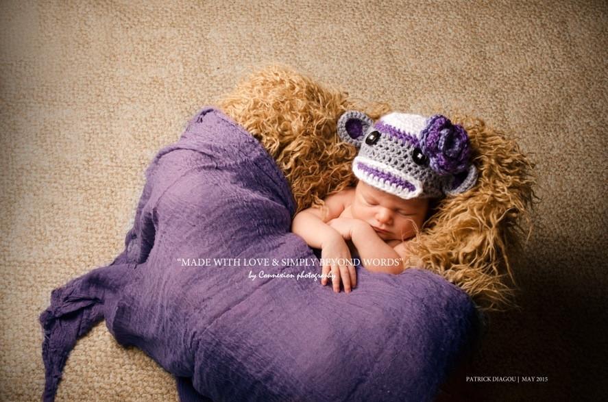 Bébé blanc à moitié couvert d'un drap violet et un bonnet en laine dort sur fourrure beige