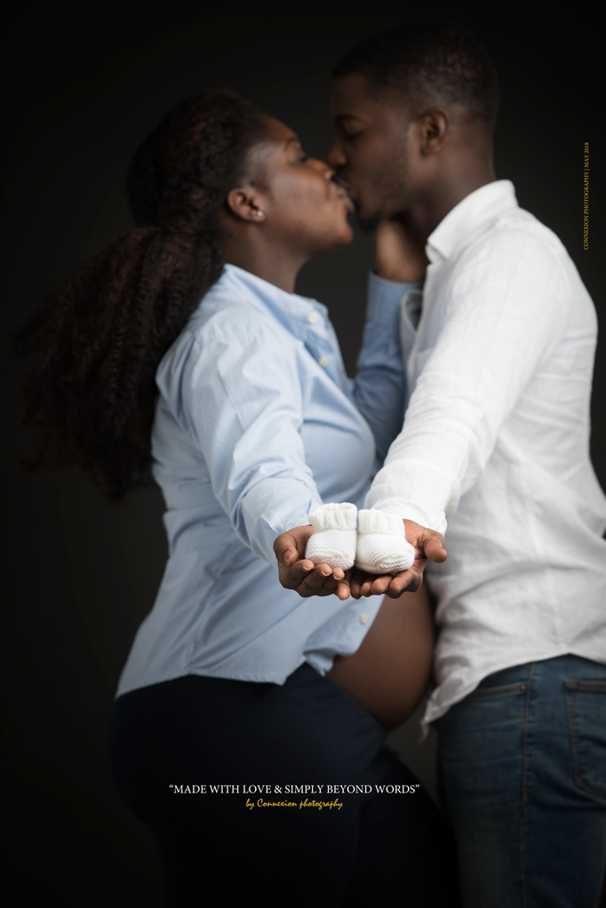 Papa et maman enceinte noire tiennent les chaussons du futur bébé en s'embrassant