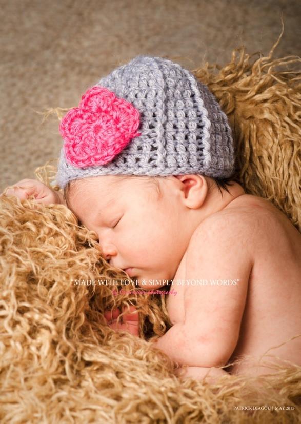 Bébé blanc nu avec bonnet en laine violet endormi sur le côté sur fourrure beige