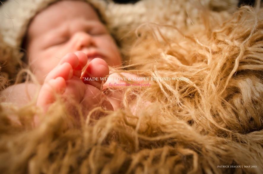 Doigts de pieds bébé blanc nu avec bonnet en laine beige endormi sur fourrure beige