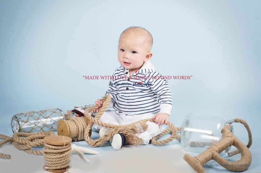 Bébé blanc en tenue de marin à rayures noires et blanches, légèrement de profil souriant assis dans un décor marin sur fond bleu
