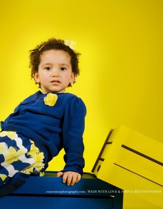 enfant pull bleu assis sur caisse