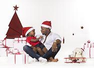 Petite fille assise sur le pieds de papa sur un décor de nöel