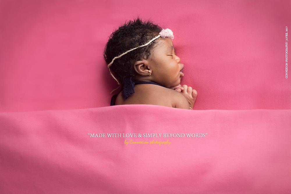 bébé noir endormi sur le ventre sous une couvert rose sur fond rose