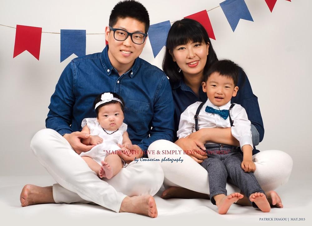 Petite famille asiatique, papa et maman assis sur le sol leurs enfants sur les pieds