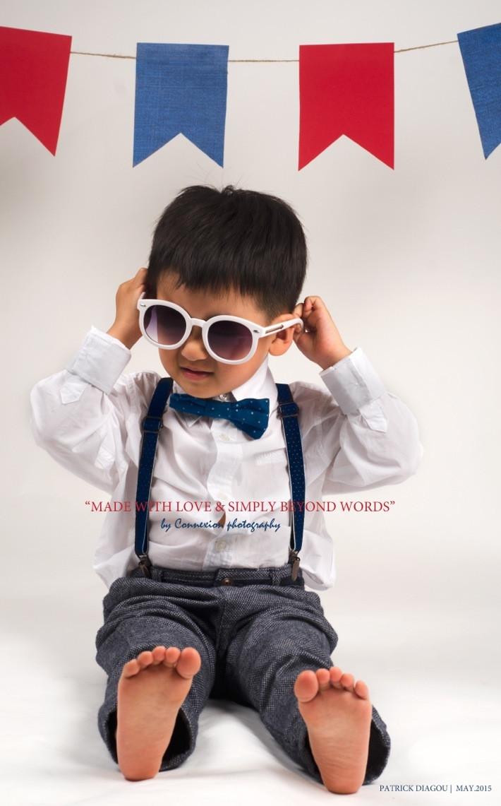 Enfant asiatique assis sur le sol en tenue de soirée tient ses es lunettes de soleil