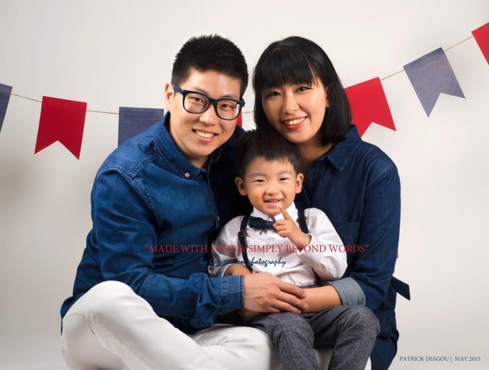 Famille asiatique papa et maman assis sur le sol leur enfant sur les pieds de maman