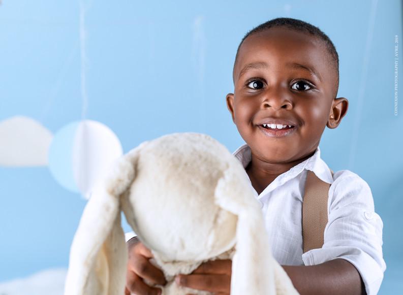 Enfant noir debout sur fond bleu tient sa peluche en souriant