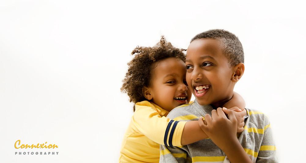 Petite fille noire sur le dos de son frère  assis tous deux souriant
