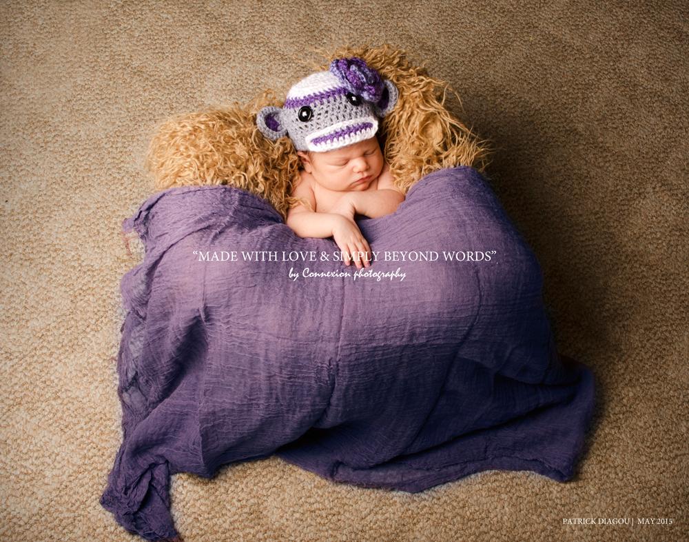 Bébé blanc à moitié couvert d'un drap violet dort sur fourrure beige