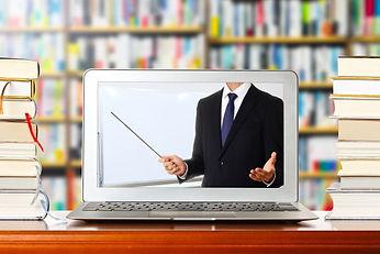 本棚とパソコンに映った指し棒を持った男性
