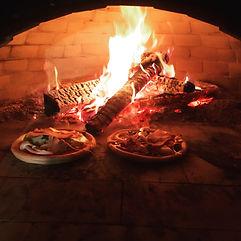 石窯で薪を使ってピザを焼く