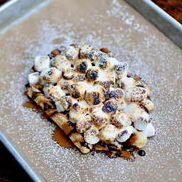 S'MORES! Fire toasted mini marshmallows, chocolate syrup, and cookie butter (aka liquid graham crackers) on top of our golden Liége waffle.