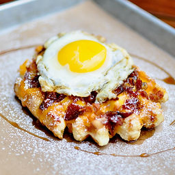Our golden Liége waffle smothered with melty cheddar cheese, bacon crumble, maple syrup, and topped off with a fried or scrambled egg.