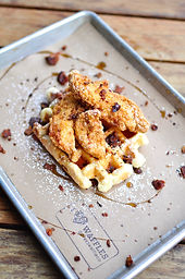 Two deep fried crispy tenders with bacon crumble and maple syrup on top of our golden Liége waffle.