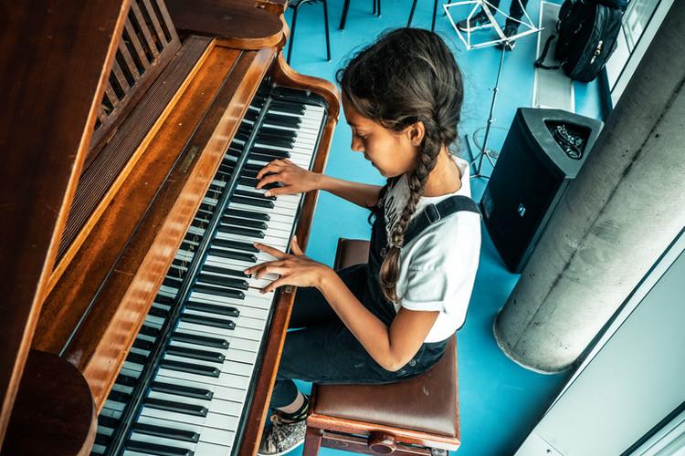 pige sidder og spiller klaver