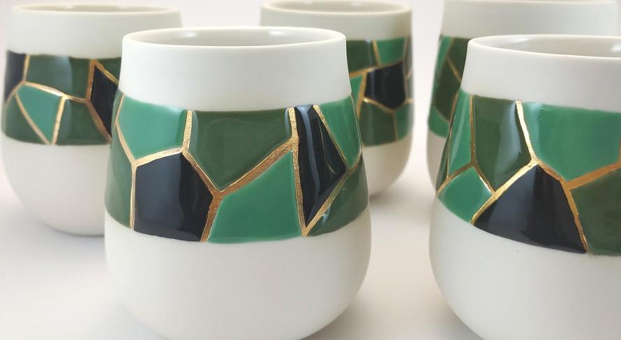 Série de gobelets en porcelaine tournés à la main. Décor en émail cloisonné, motif mosaique noir et camaieu de vert. Chaque espace entre les couleurs est rempli à l'or.